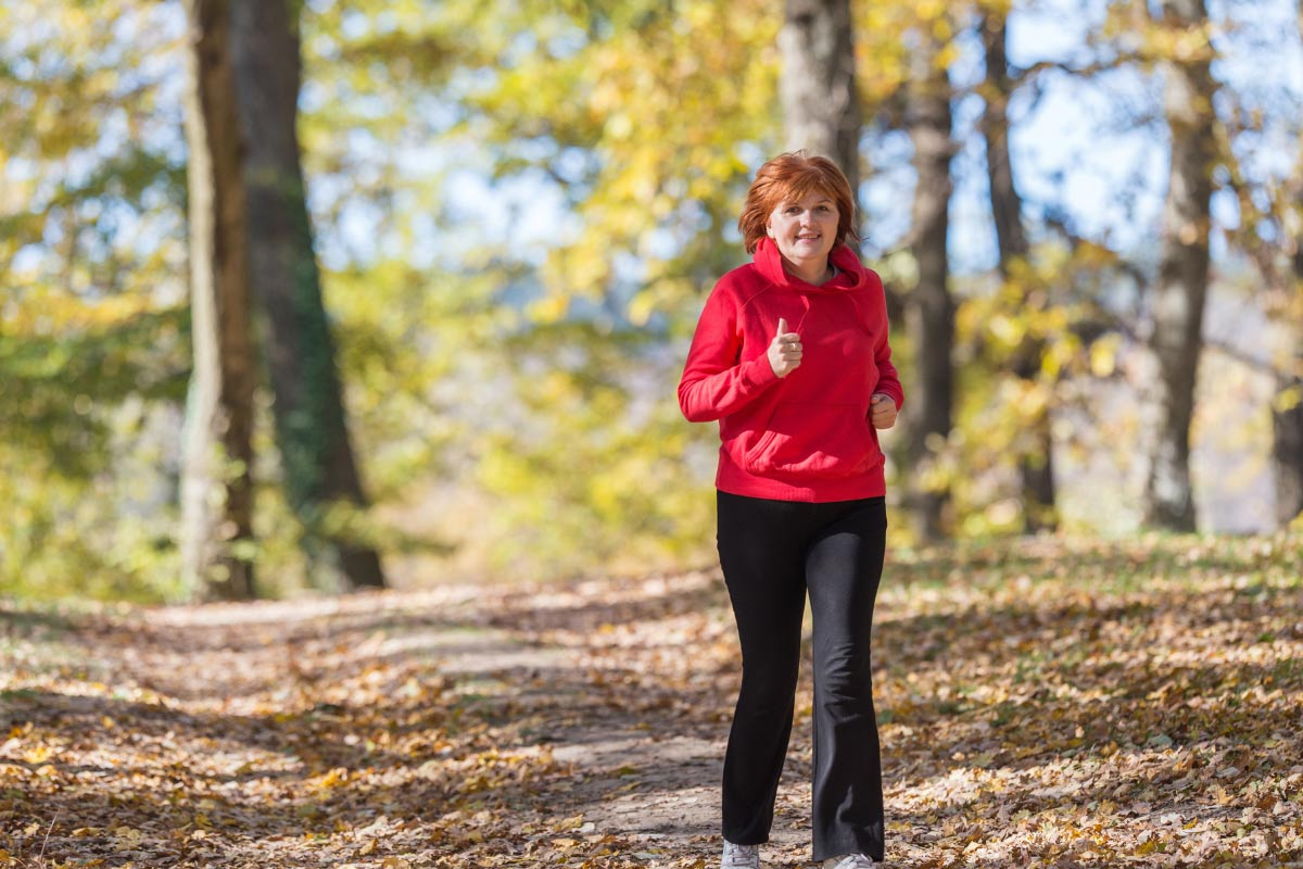 woman in red hiking in woods