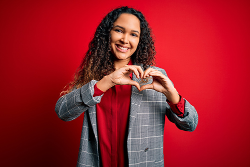 woman holding heart hands with red background
