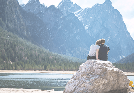 couple sitting on large rock overlooking lake and mountains