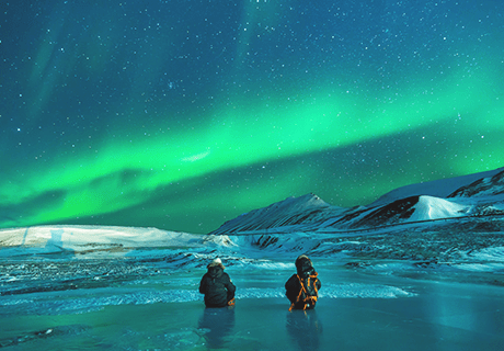 two people fishing near snow covered hills looking at the Northern Lights