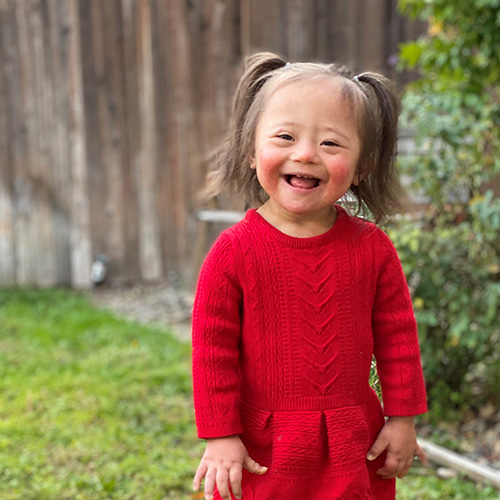 Ariel, a toddler with Down Syndrome, smiling in her backyard with a red dress and pig tails