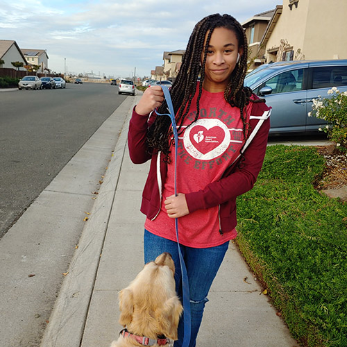 Teenager in a red American Heart Association shirt walking her dog