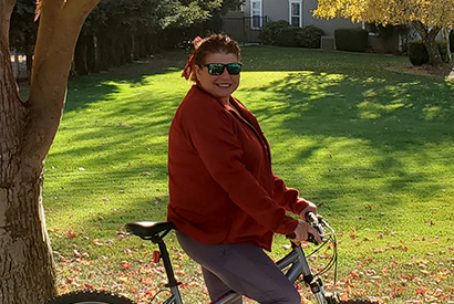 Woman in red sweater smiling on bike