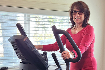 Woman smiling on an elliptical machine