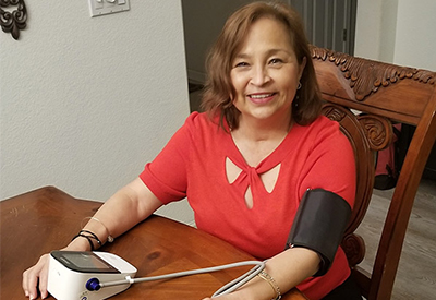 Dina Felix smiling at her kitchen table while taking her blood pressure