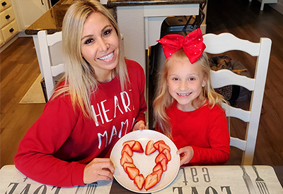 mother and daughter smiling at their kitchen table and holding up a plate of sliced strawberries in the shape of a heart