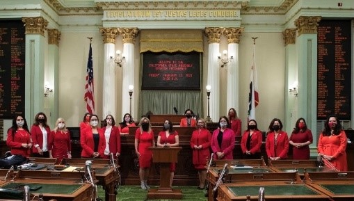 women wearing red suits and protective face masks at the California state capitol
