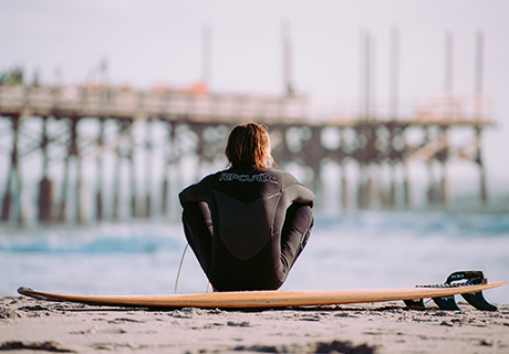 surfer sitting on surfboard on the beach looking at the pier