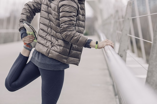 woman stretching on a bridge in winter before a run