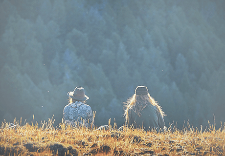 two women sitting in a field overlooking Idaho mountains