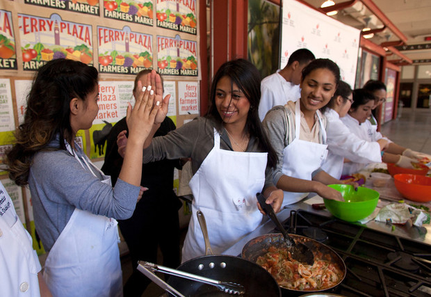 Kids high five as they cook. Gallileo High School junior Maria Salvador, left, and senior Dina Moncada-Choukri high five each other at the conclusion of their Iron Chef-style cookoff against Mt. Diablo High School students at the Bay Bridge Teens Cook with Heart Challenge at the Ferry Building in San Francisco, March 17, 2014. (D. Ross Cameron/Bay Area News Group)