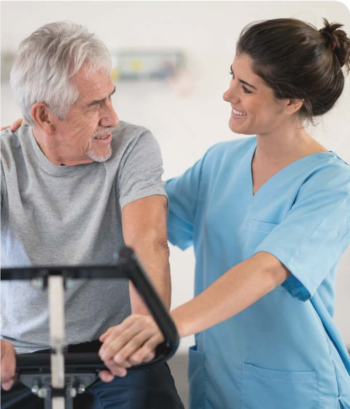 man smiling at nurse while on a cycle machine in cardiac rehab