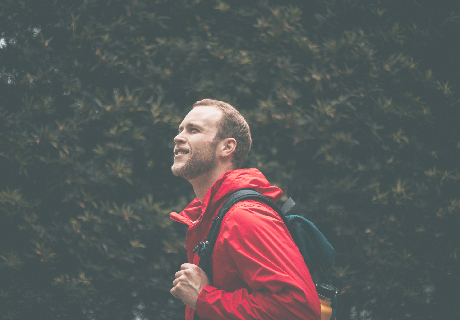 Man in red jacket with backpack standing against foliage wall