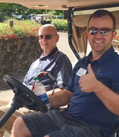 Two smiling men in a golf cart