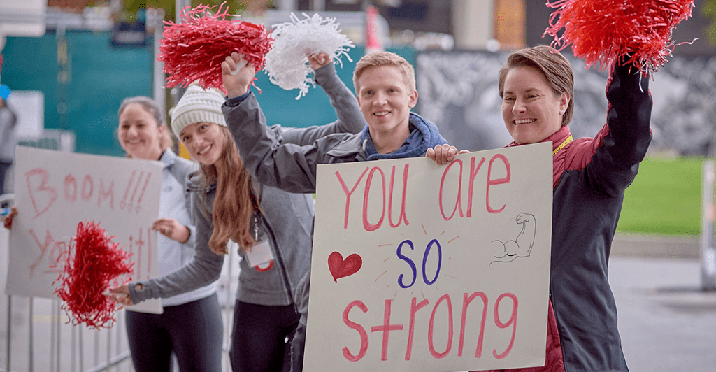 volunteers holding inspiration signs and cheering at Heart and Stroke Walk finish line