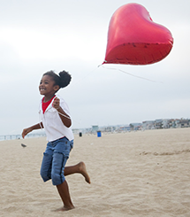 Child on the beach with a heart balloon
