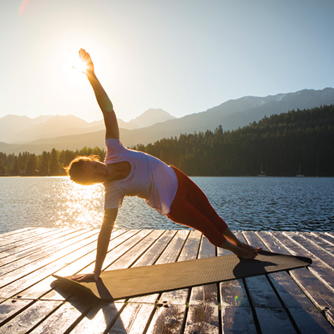 Woman doing yoga on a dock near a lake