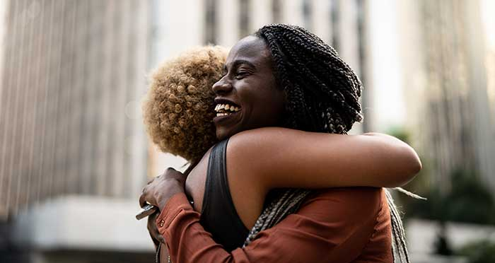 two happy women hugging in downtown setting
