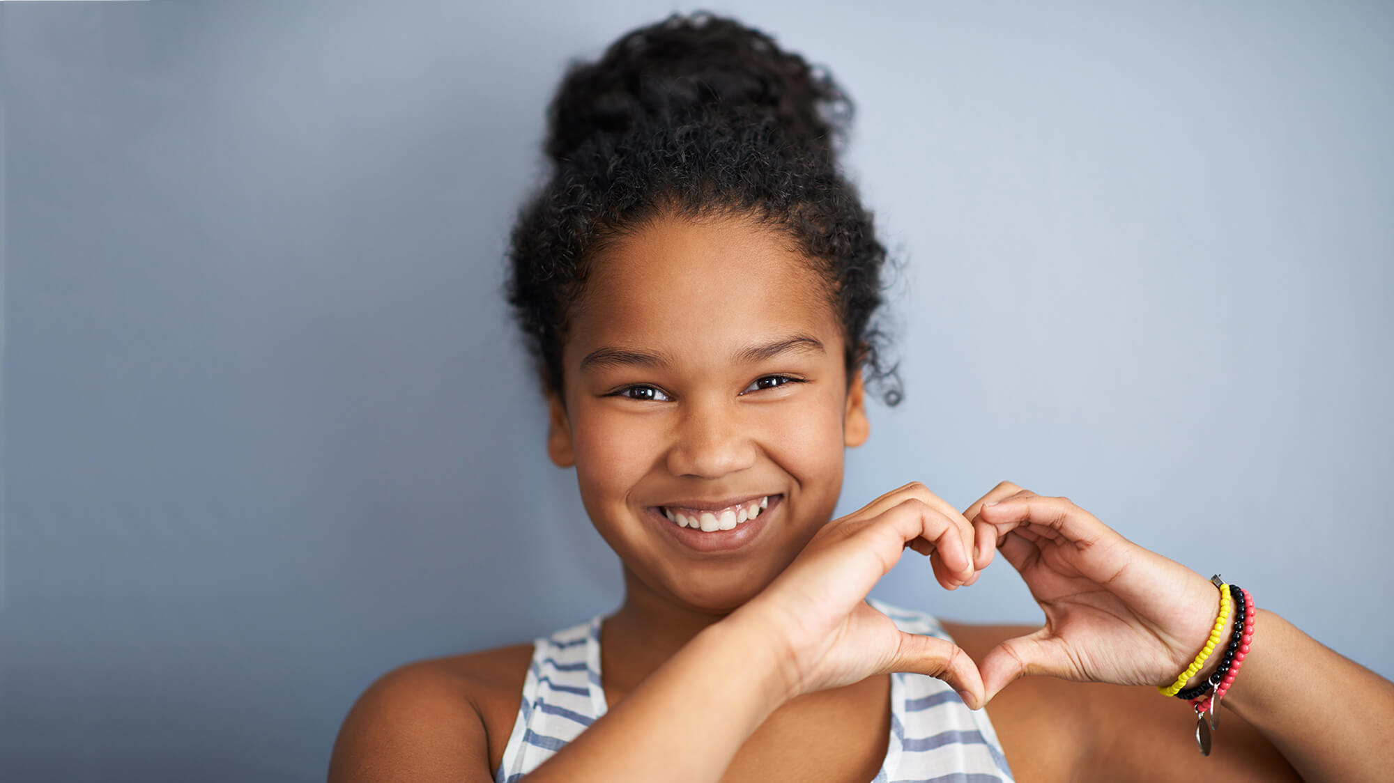 Young smiling girl making a heart with her hands