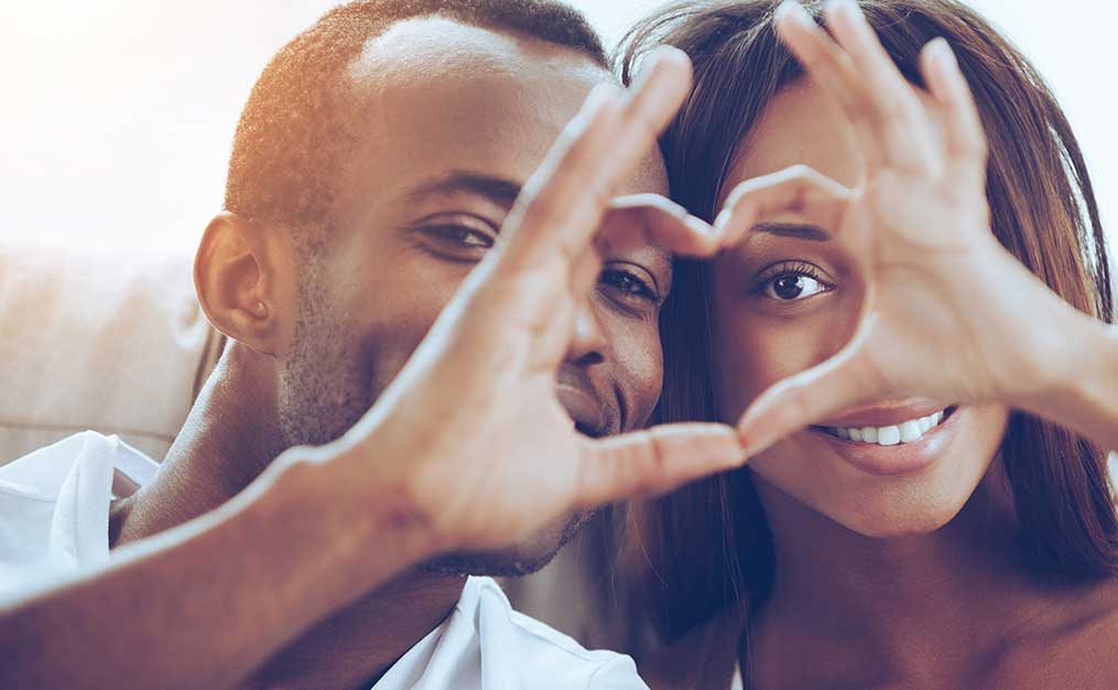 african american couple making heart sign with their hands