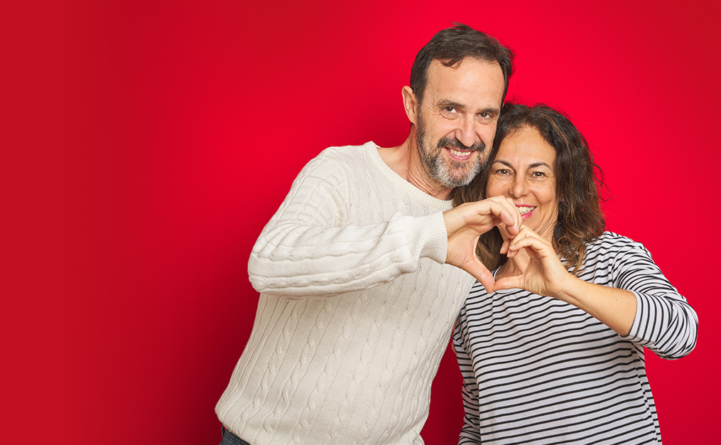 man and woman couple smiling at camera and making heart sign with their hands