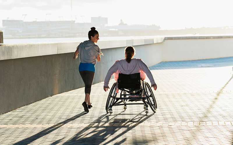 Woman in wheelchair with another woman jogging