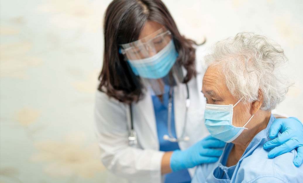 female doctor with elderly female patient. both wearing protective masks