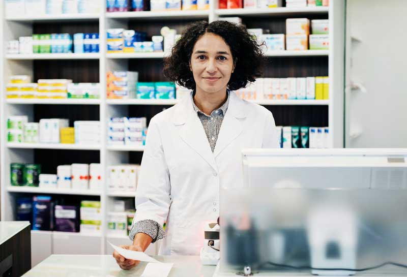 pharmacist holding prescription behind the counter