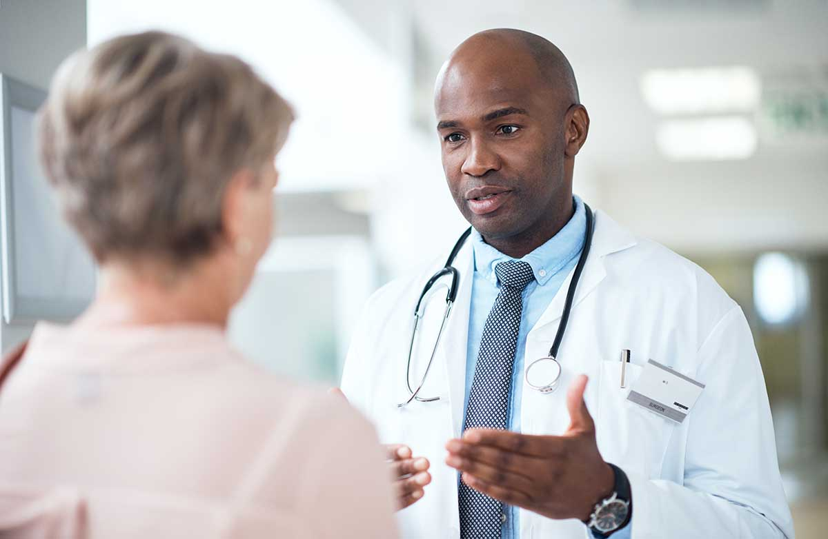 male doctor speaking with female patient