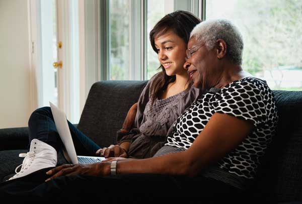 Grandmother and granddaughter researching on laptop