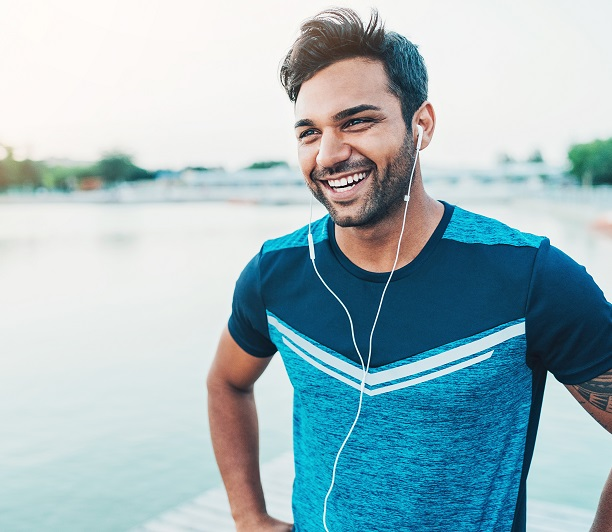 man exercising outdoors while listening to music and smiling
