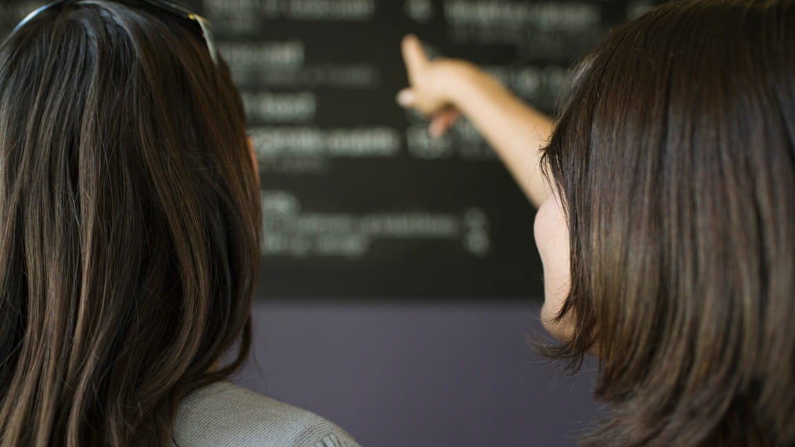women choosing from menu board in restaurant