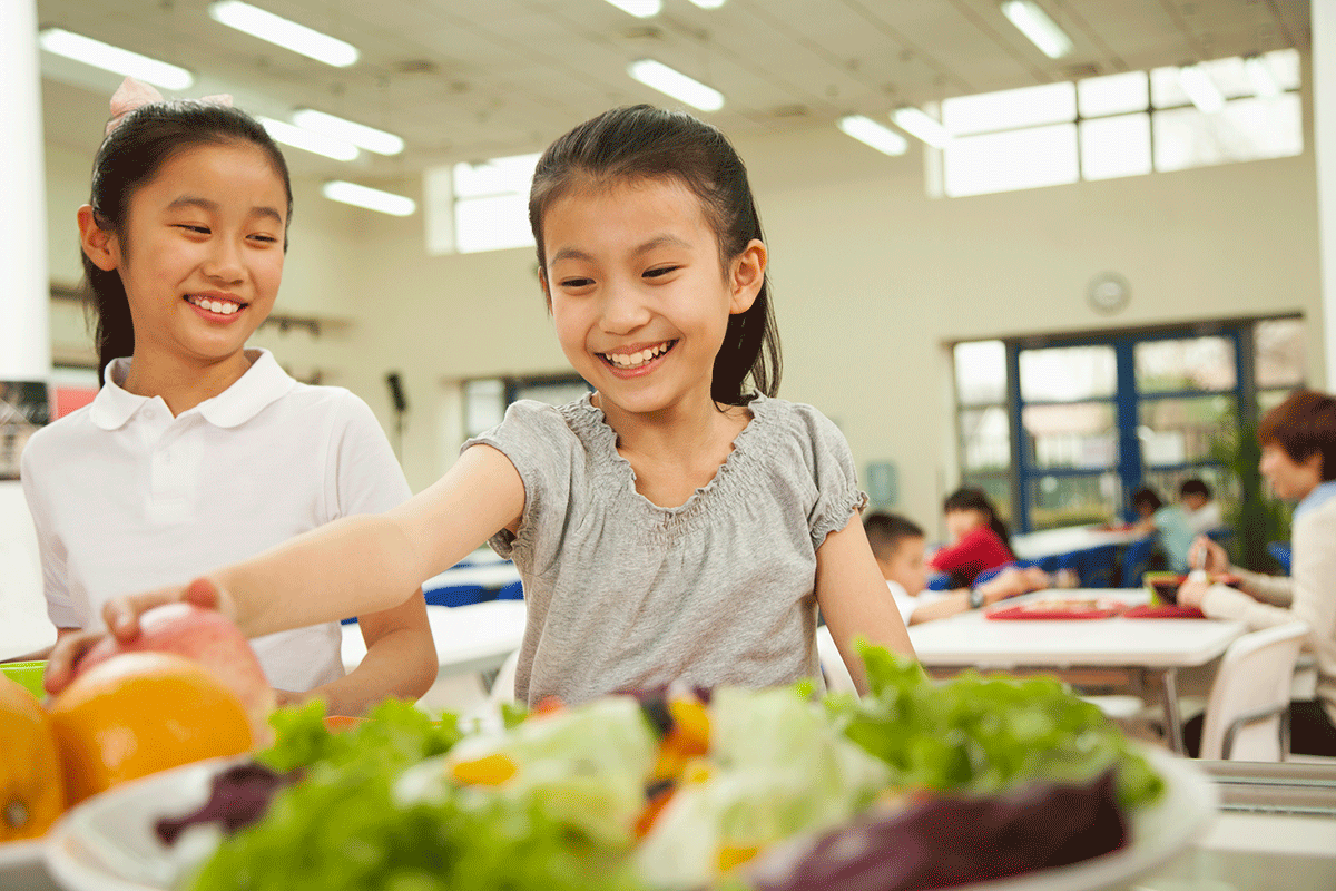 happy elementary students choose food in school lunch line