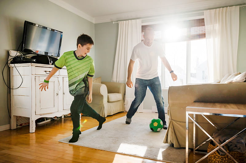 dad and son play indoor soccer at home