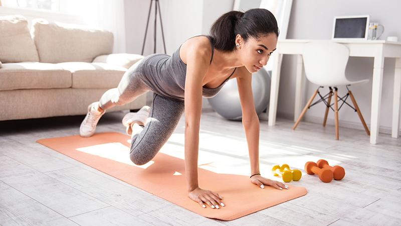 Woman doing yoga or pilates on mat in home