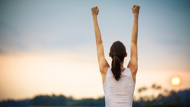 successful woman raising arms in triumph