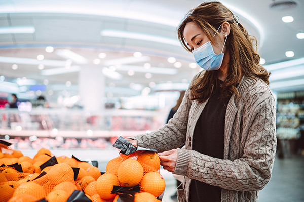 woman grocery shopping wearing mask