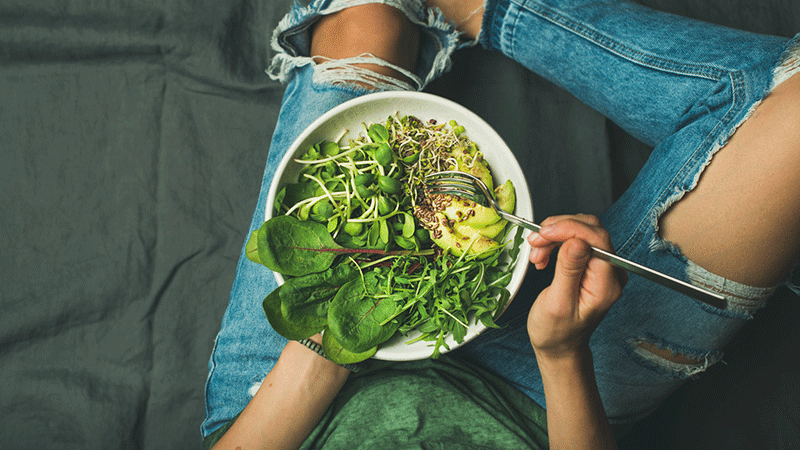 woman in ripped jeans eating salad