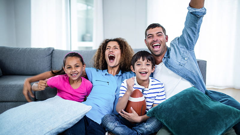Family watching american football match on television at home