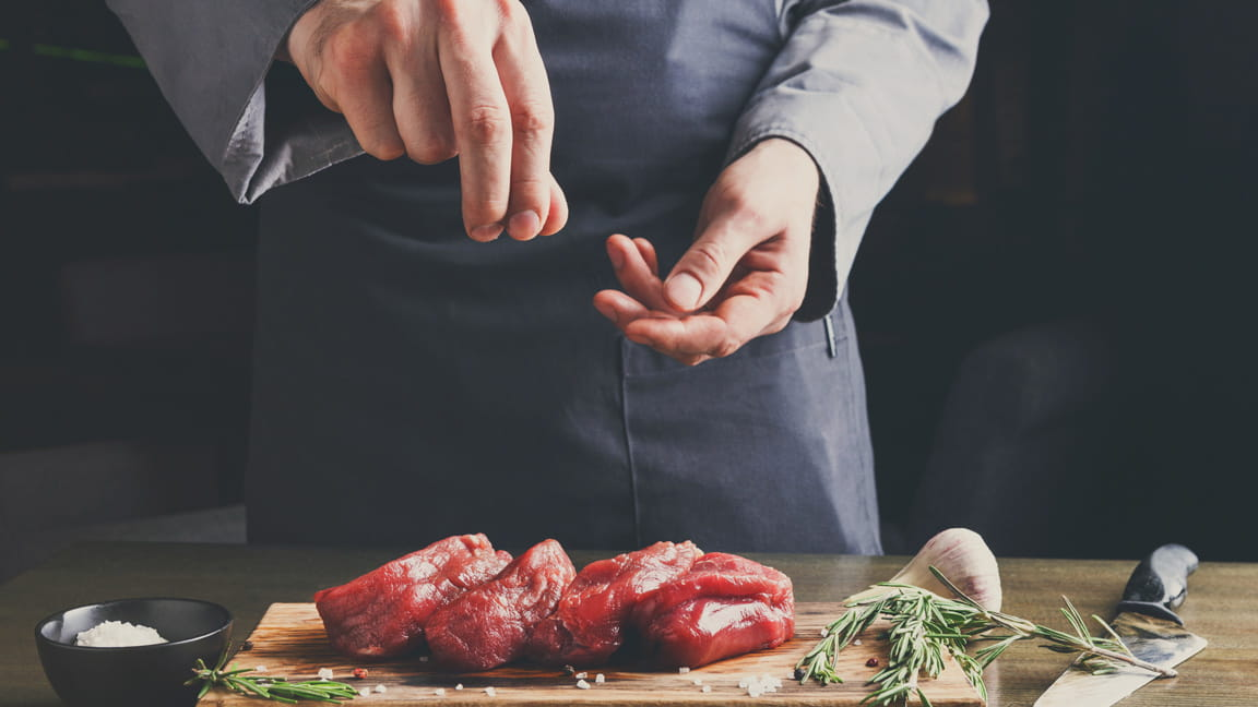 man's hands adding salt to meat while cooking