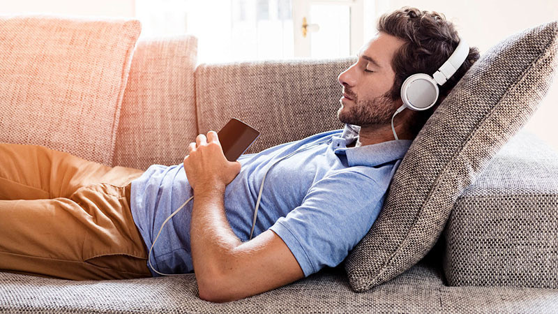 Man laying on couch listening with headphones