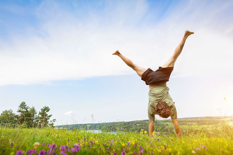 Young man doing a handstand in a grassy field