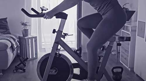 woman riding stationary bicycle