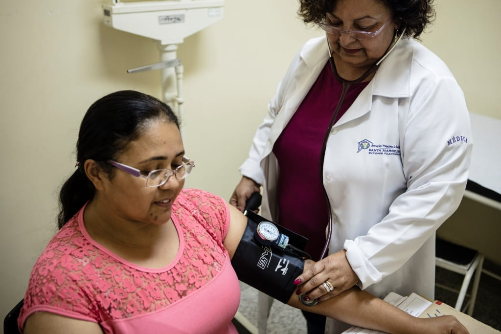 Female doctor taking woman's blood pressure