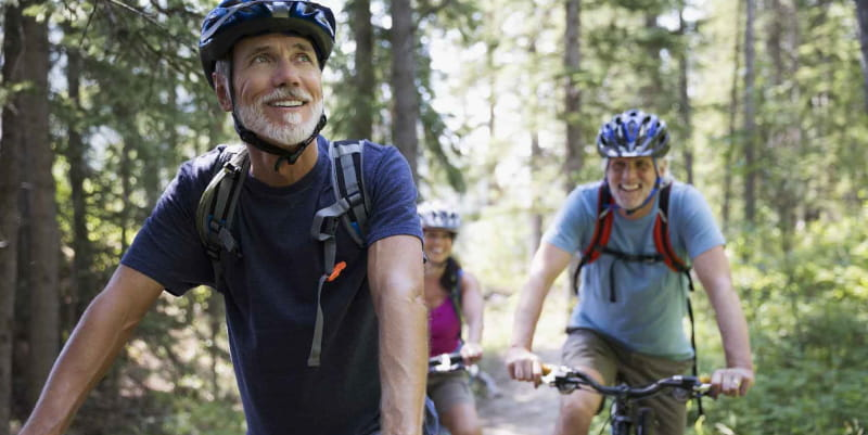 Older couple riding bikes on a trail