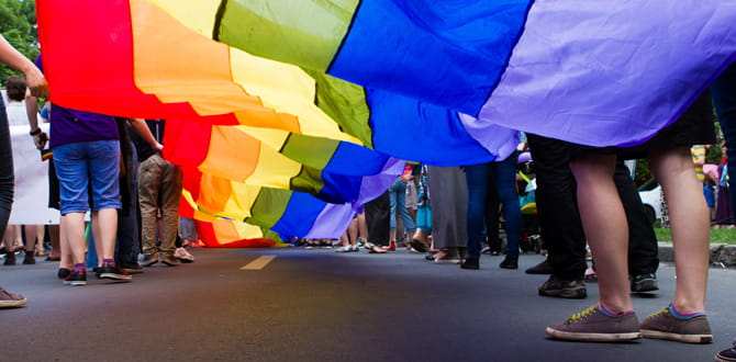 People holding a rainbow-colored  parachute.