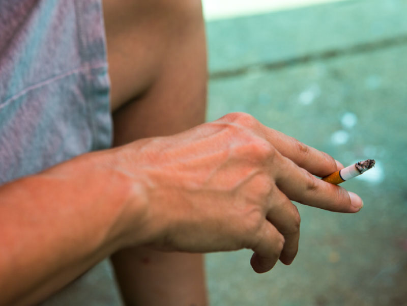 Person's hand holding cigarette. (Amie Vanderford for AHA News)