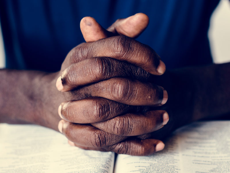 African-American man's hands, praying. (Rawpixel, Envato Elements)