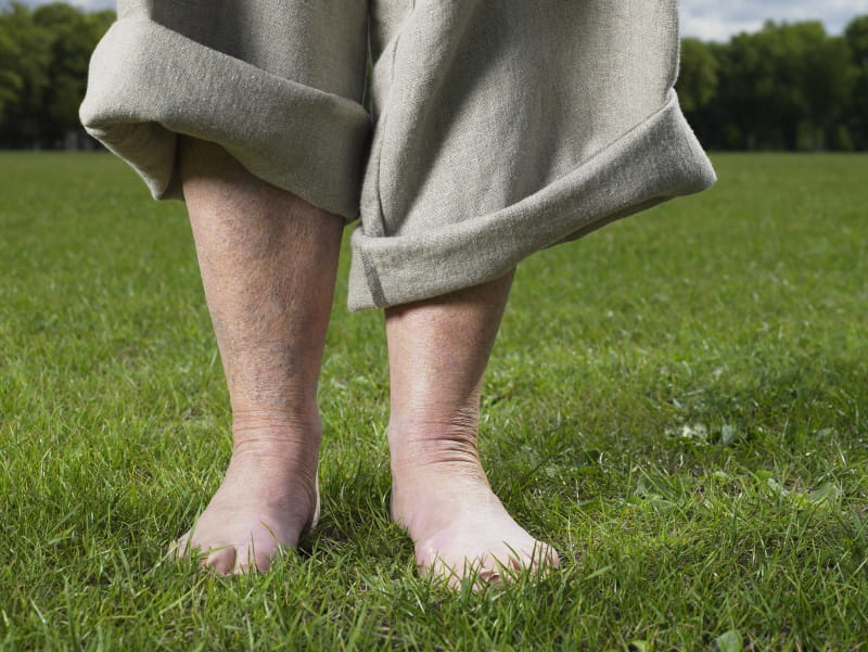 Older person walking in grass barefoot.  (Getty Images)