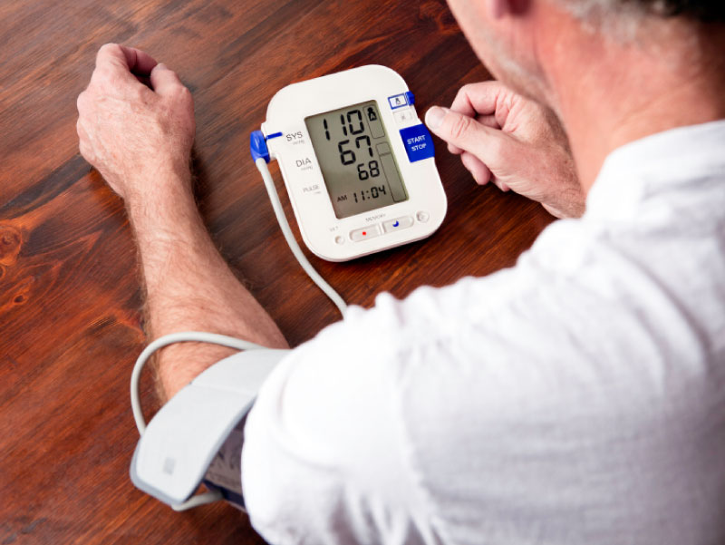 Man using blood pressure monitor. (cglade, iStockphoto)